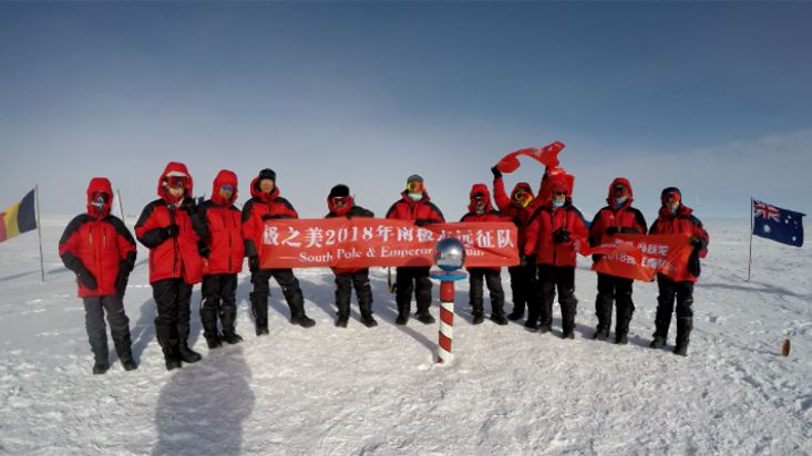 Chinese travelers jumping for joy at the ceremonial South Pole - 2018