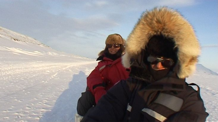 Travellers enjoying the arctic landscape in dogsled - Nanoq 2007 expedition